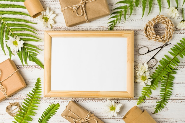 Elevated view of blank frame surrounded by gifts; leaves and white flowers Free Photo