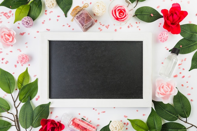 Elevated view of blank frame surrounded with cosmetic products and leaves on white surface Free Photo