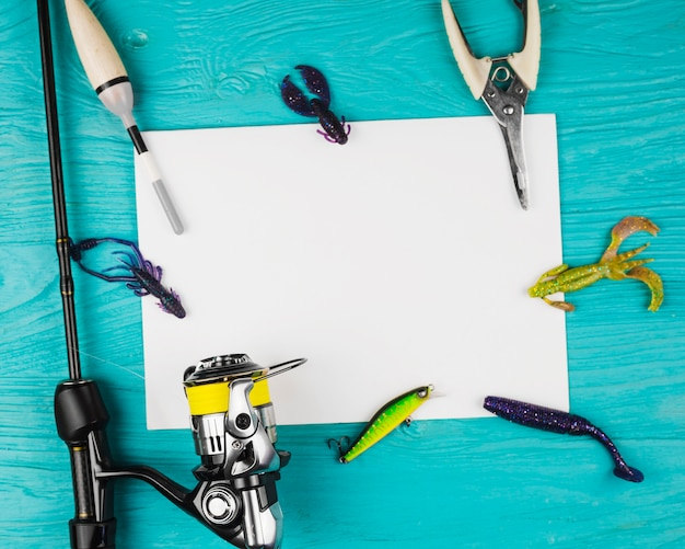 Elevated view of blank paper with various fishing equipment on turquoise backdrop Free Photo