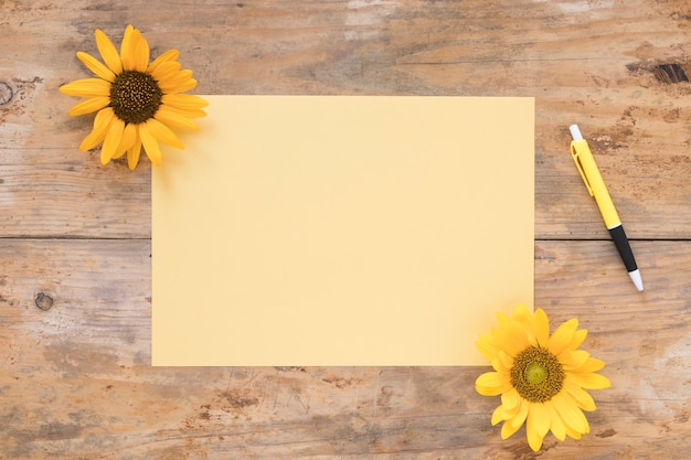 Elevated view of blank paper with yellow sunflowers and pen on wooden backdrop Free Photo