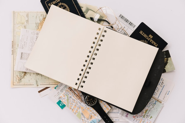 Elevated view of blank spiral notebook on passports and maps against white background Free Photo
