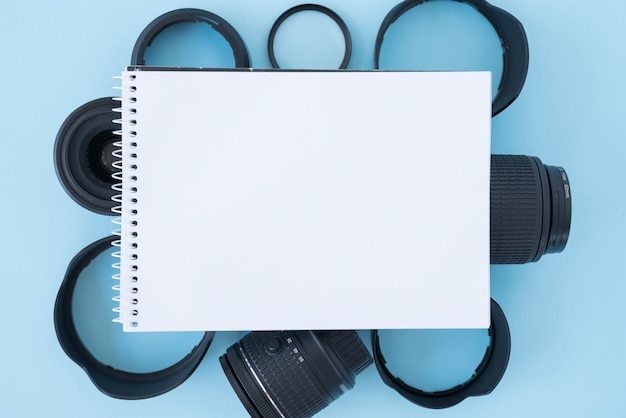 Elevated view of blank spiral notepad over camera ...