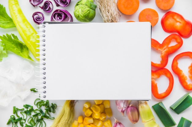 Elevated view of blank spiral notepad over fresh healthy vegetables Free Photo