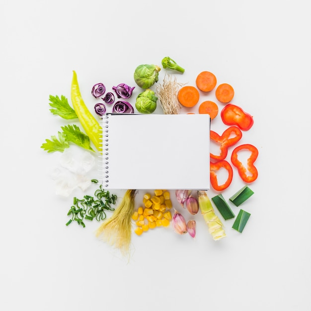 Elevated view of blank spiral notepad on fresh vegetables over white background Free Photo