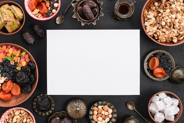 An elevated view of blank white paper surrounded with delicious dried fruits; nuts and sweets for ramadan on black textured backdrop Free Photo