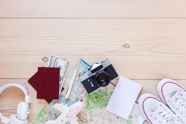 Elevated view of blank white paper and traveler accessories on wooden surface Free Photo