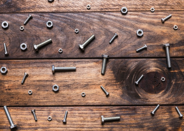 Elevated view of bolts and nuts on wooden background Free Photo