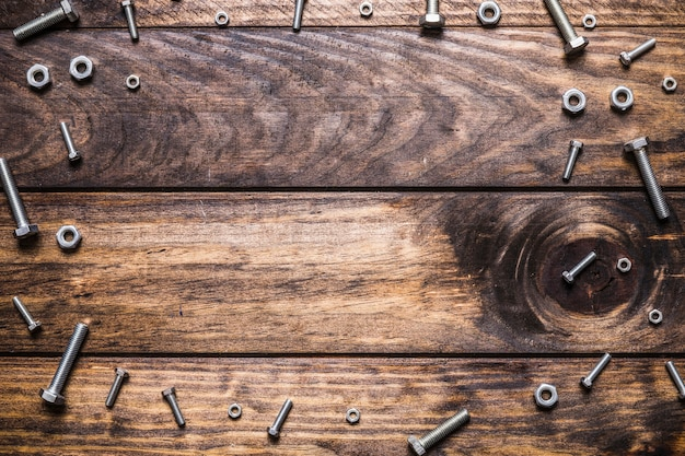Elevated view of bolts and nuts on wooden plank Free Photo
