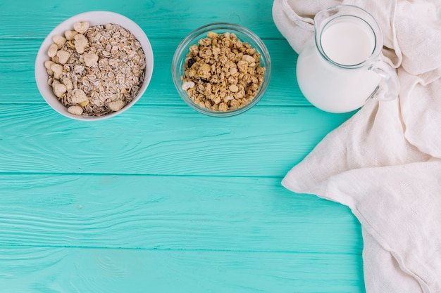 Elevated view of bowls of cereals; milk jar on green wooden table Free Photo