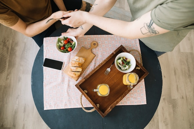 Elevated view of breakfast and mobile phone on table in front of men Free Photo