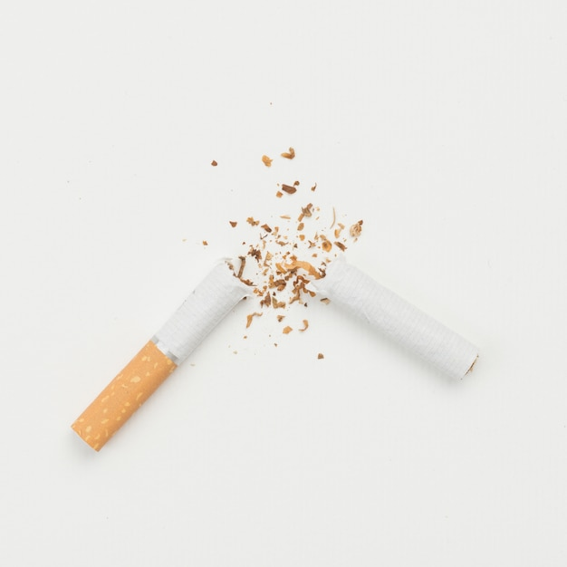 Elevated view of broken cigarette on white backdrop Free Photo