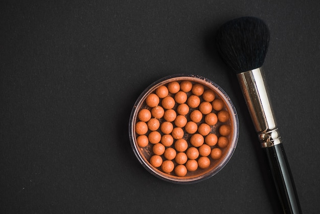 Elevated view of bronzing pearls and makeup brush on black surface Free Photo