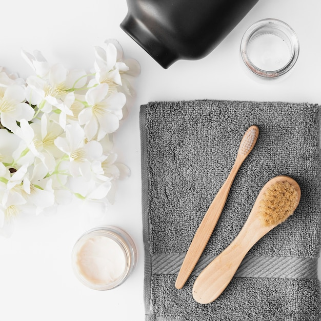 Elevated view of brush; towel; moisturizing cream; flowers and container on black backdrop Free Photo