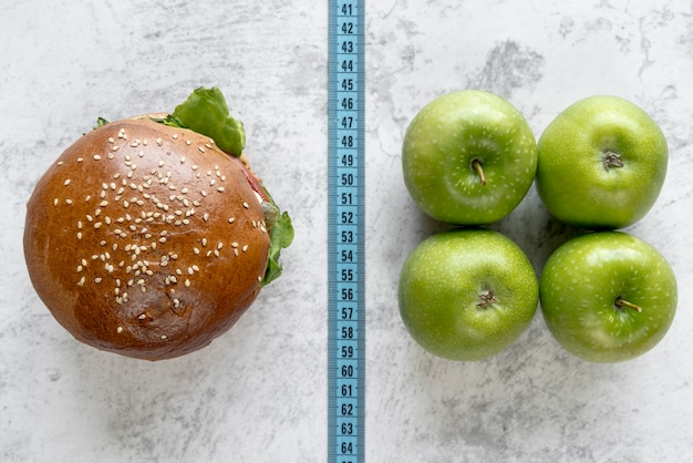Elevated view of burger and apple compare with measurement tape Free Photo