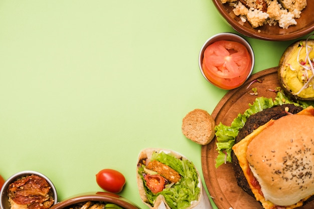 An elevated view of burrito wrap; salad and hamburger on green background Free Photo