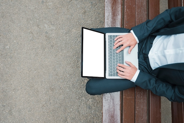 An elevated view of businessman sitting on bench typing on laptop Free Photo