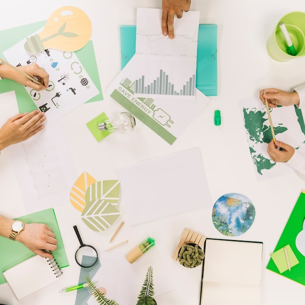 Elevated view of businesspeople hand with various natural resources icon on desk Premium Photo