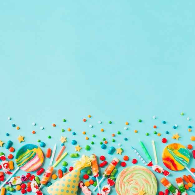 Elevated view of candies; party hat and candles on blue backdrop Free Photo