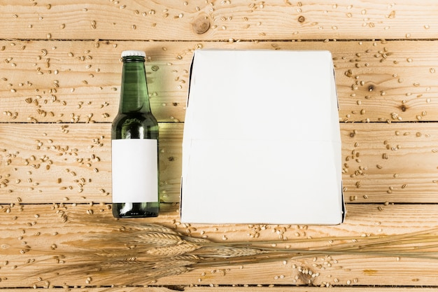 Elevated view of carton box; beer bottle and ears of wheat on wooden background Free Photo