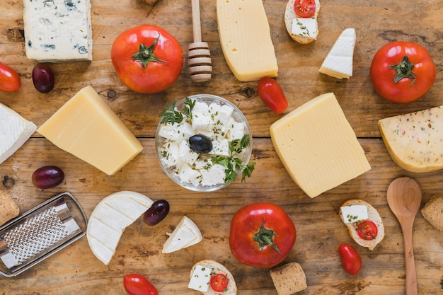 An elevated view of cheese blocks with tomatoes; grapes on wooden table Free Photo