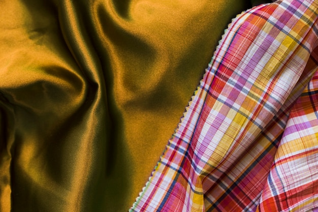 Elevated view of chequered pattern table cloth on silky golden textile Free Photo