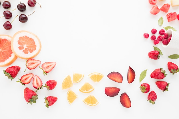An elevated view of cherries; grapefruit; strawberries; lemon; plums; strawberries; watermelon and raspberries on white backdrop Free Photo