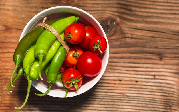Elevated view of cherry tomatoes and green chili peppers on wooden surface Free Photo