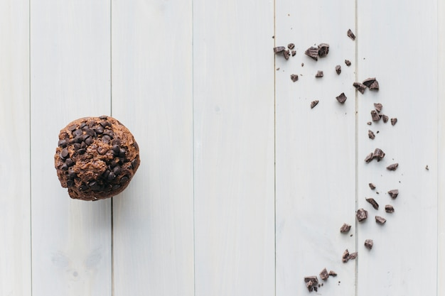 Elevated view of choco chip cupcake and scattered chocolate on wooden background Free Photo