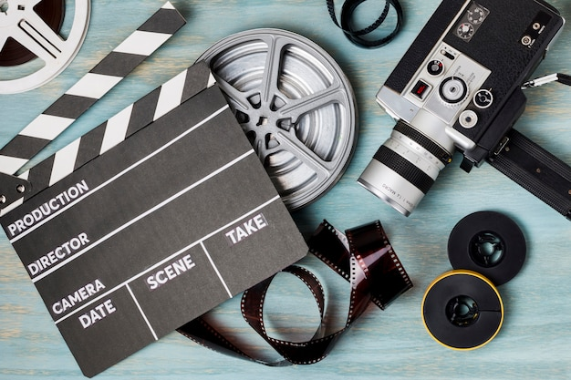 An elevated view of clapperboard; film reels; film strips and camcorder on blue wooden backdrop Free Photo