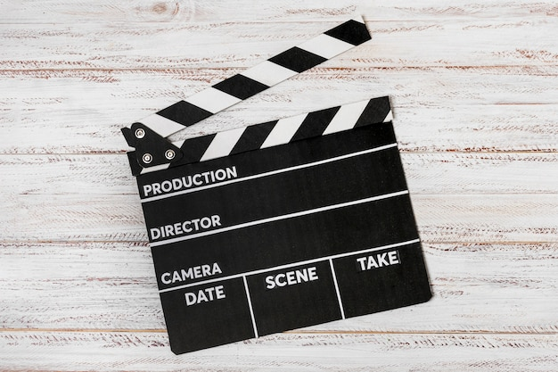 An elevated view on clapperboard over white wooden desk Free Photo