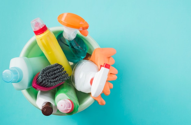 Elevated view of cleaning products in bucket in turquoise background Free Photo