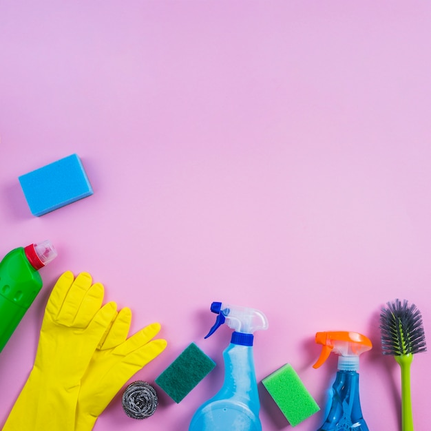 Elevated view of cleaning products on pink background Free Photo
