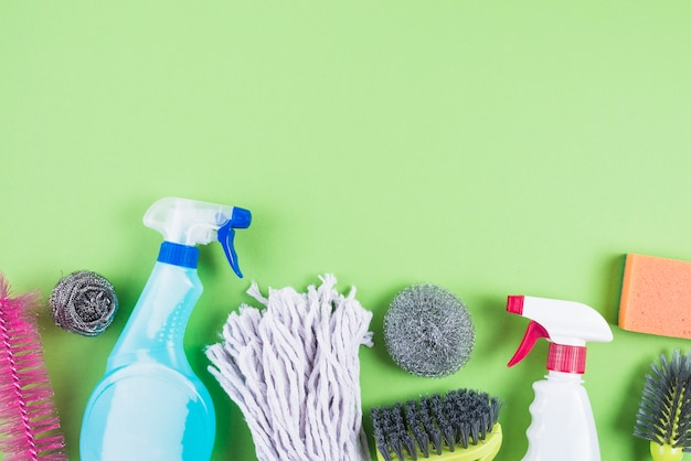 Elevated view of cleaning supplies on green backdrop Free Photo