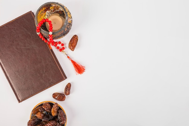 An elevated view of closed diary with prayer beads and fresh dates on white backdrop Free Photo