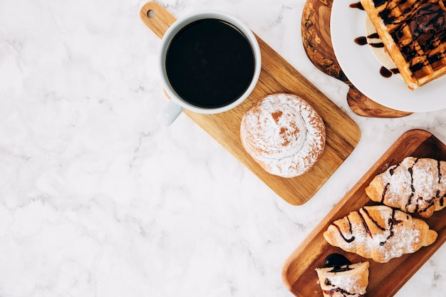 An elevated view of coffee cup; baked buns; croissant and waffles on wooden tray against marble textured background Free Photo