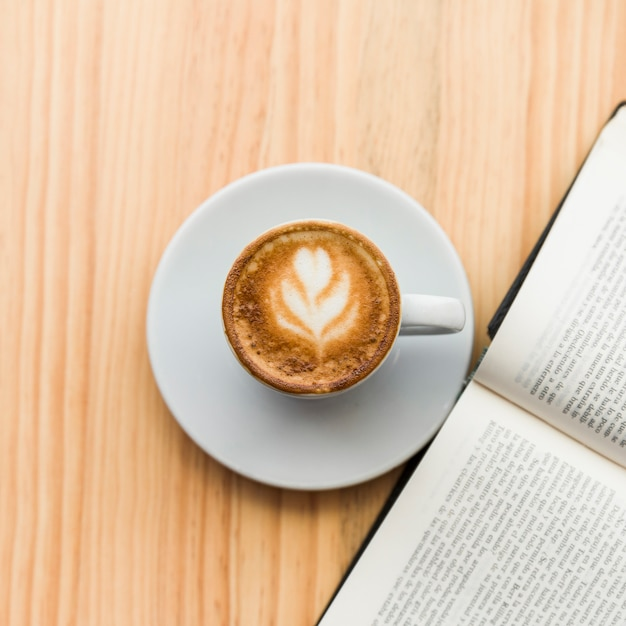 Elevated view of coffee latte and open book on wooden background Free Photo
