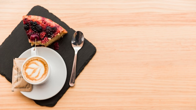 Elevated view of coffee latte and pastry on wooden table Free Photo