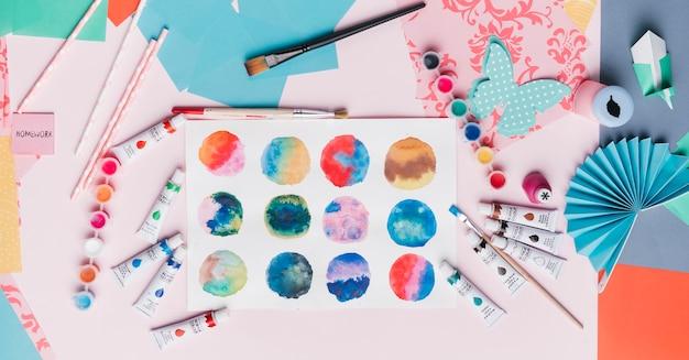 Vista elevata della pittura astratta colorata del cerchio; cannuccia; origami; e attrezzatura per la pittura Foto Gratuite