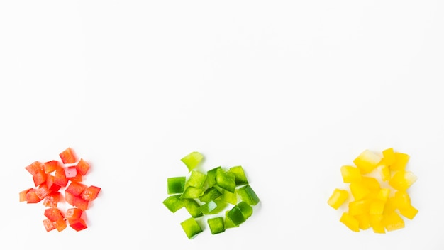 Elevated view of colorful chopped bell peppers on white backdrop Free Photo