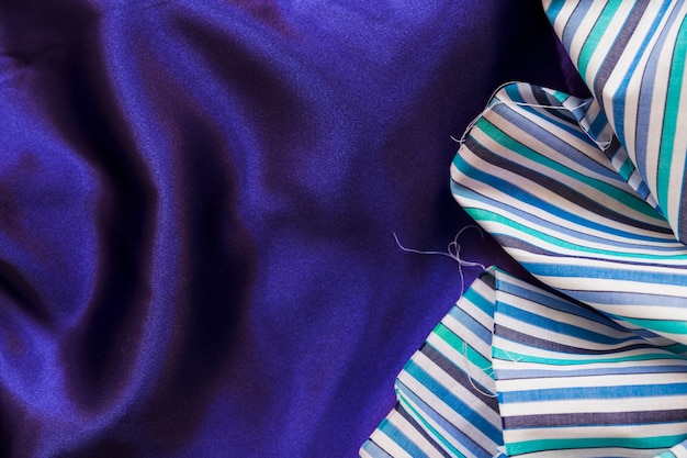 Elevated view of colorful fabric material on smooth purple textile Free Photo