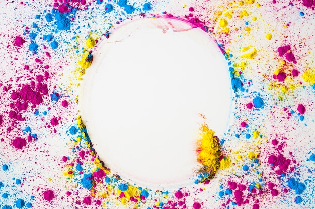 Elevated view of colorful face powder forming circular frame on white surface Free Photo