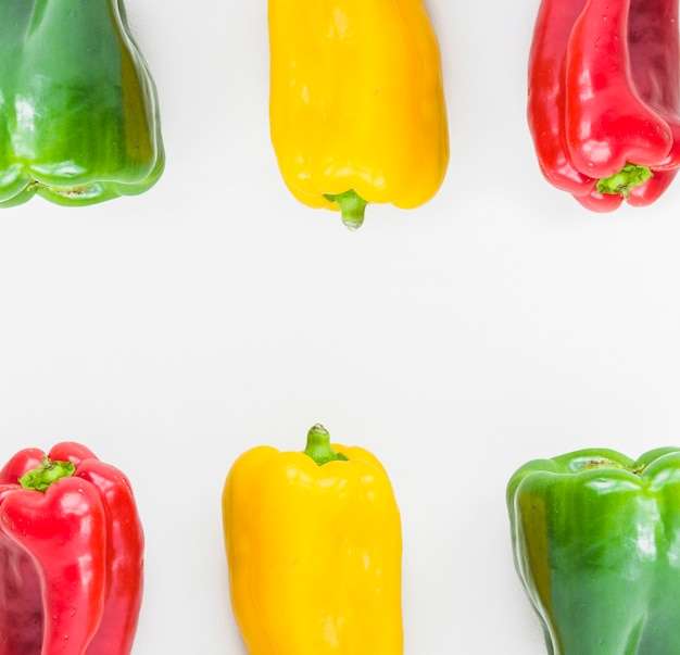 Elevated view of colorful fresh bell peppers on white backdrop Free Photo