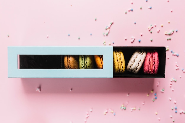 Elevated view of colorful macaroons in a box on pink background Free Photo
