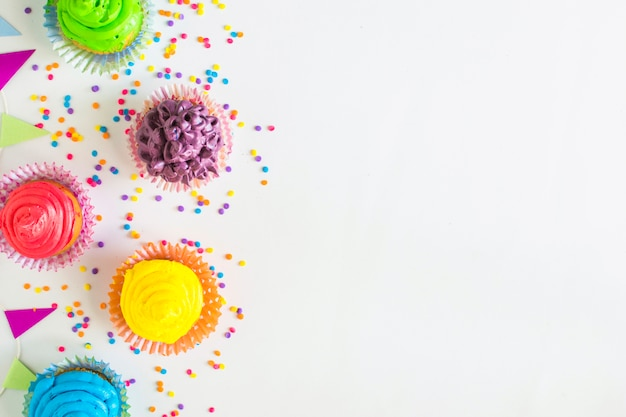Elevated view of colorful muffins and bunting on white surface Free Photo