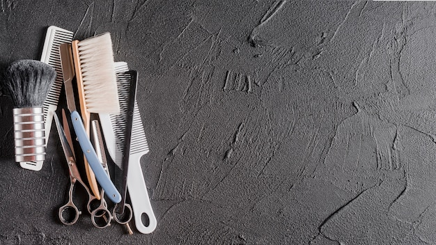 Elevated view of combs, scissors and razor on black surface Free Photo