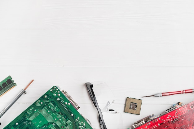 Elevated view of computer circuit boards and chip with tools on wooden background Free Photo