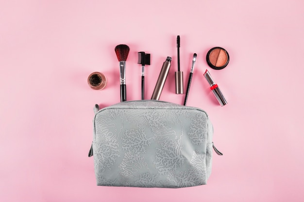 Elevated view of cosmetic bag containing lipstick; mascara; eyeliner and brushes on pink background Free Photo