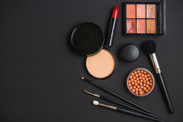 Elevated view of cosmetic products and brushes on black background Free Photo