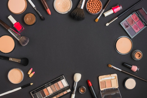 Elevated view of cosmetic products forming circular frame on black background Free Photo