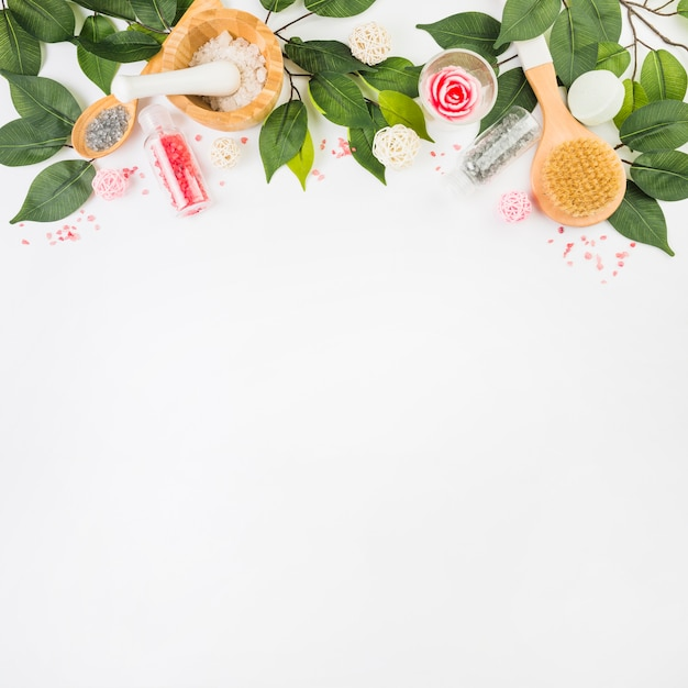 Elevated view of cosmetic products and green leaves at the top of white background Free Photo